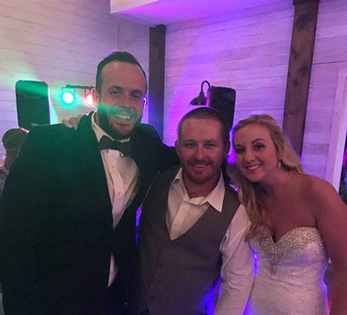 DJ Dom posing with the bride and groom