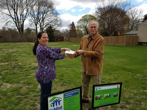 Denise Franz presenting Habitat for Humanity Board Member Lee McCullough the April 2019 Donation
