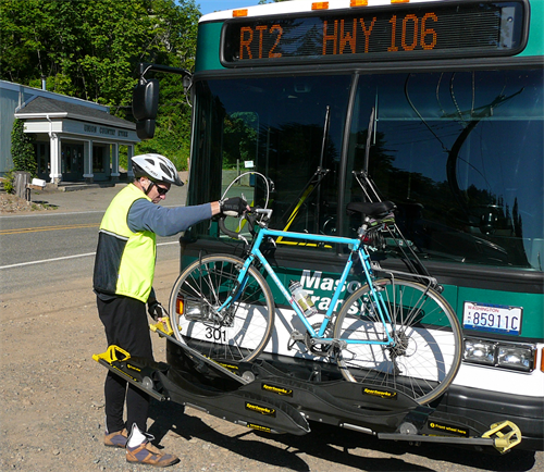 Passenger loading their bike before boarding an MTA bus. Bring your bike when you travel on an MTA bus!  Our drivers will help you if you've never loaded a bike!