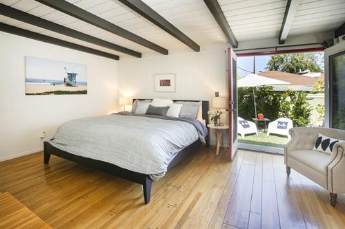 Beautiful master bedroom with wood beam ceiling leading to fantastic backyard oasis!