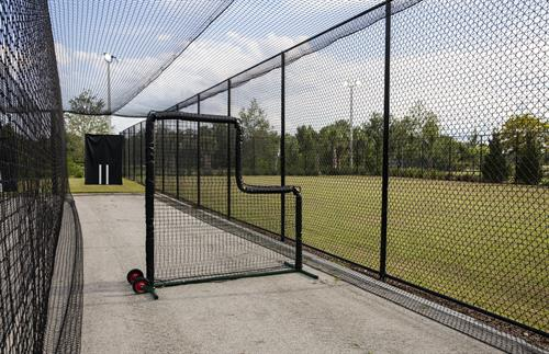 Athletic facilities featuring sports practice fields with batting cages