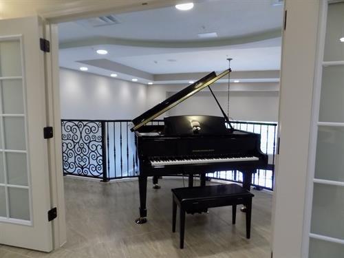 Our beautiful baby grand piano sits on the 2nd floor balcony, overlooking our lobby.