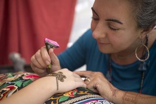 Applying henna at art festival