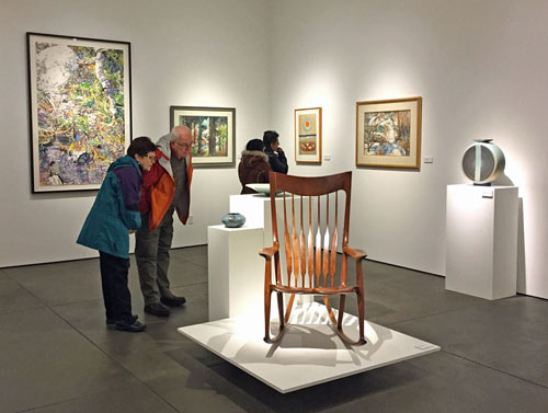 Visitors look at a chair by Sam Maloof in the ReGeneration exhibition.