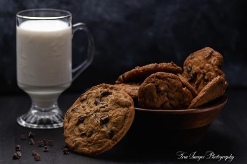 Bowl of chocolate chip cookies and glass of milk
