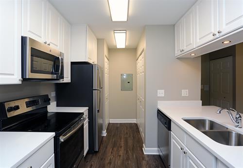 White cabinets, quartz countertops & plank flooring
