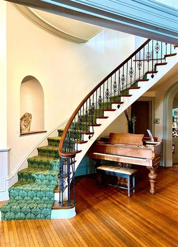 Baby grand piano accompanies the winding staircase nicely in the foyer.