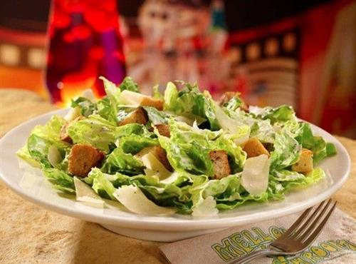 Romaine lettuce tossed with Caesar dressing and topped with shaved parmesan and house-made croutons.
