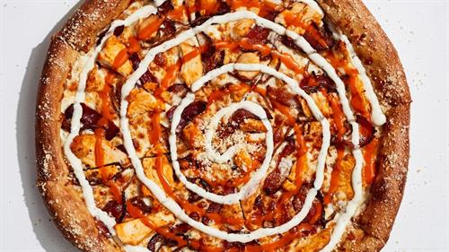 Our Buffalo Chicken pizza features mozzarella, all-natural buffalo chicken, caramelized onions, and applewood smoked bacon with a swirl of buffalo sauce. Served with a swirl of your choice of bleu cheese or ranch dressing.