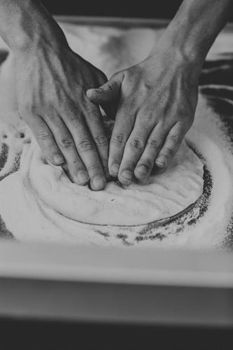 One of our Pizza Chefs stretching out our homemade dough!