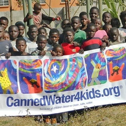 Children in Zambia, Africa posing with banner after completion of a sustainable well project.