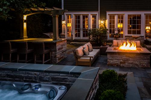 We turned an undersized patio into a relaxing retreat with a fire table, outdoor kitchen, and beautifully disguised hot tub.