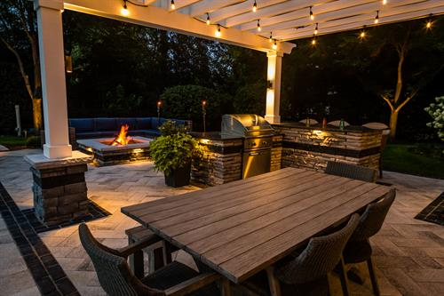 A mix of subtle landscape lighting and festive cabana lights create a safe and inviting family space.