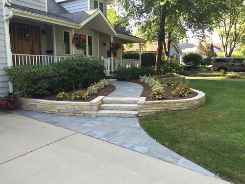 The curved bedline draws the eye to the entrance, while bluestone and flagstone complement the house perfectly.