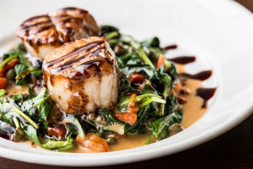 Seared scallops with capers, tomatoes, spinach, in a white wine sauce.