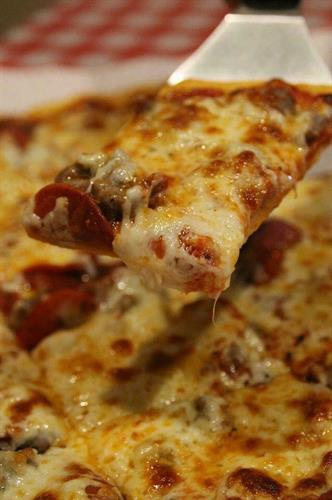 Our classic crust with our homemade italian sausage hiding underneath the cheese.