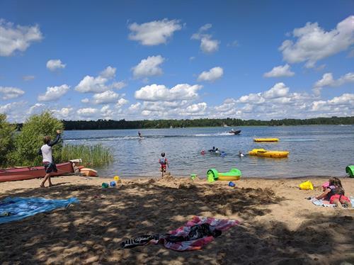 Sandy beach with canoes, kayaks, paddleboats, paddleboards, swim raft, lily pad swim mat