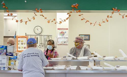 Volunteers prepare to-go hot meals to serve breakfast and lunch five days a week in the Cross-Lines Community Kitchen