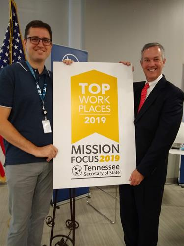 Jason Weakley and Tre Hargett with a sign showing the Secretary of State's office being awarded as one of the 2019 Top Places to Work
