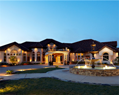Beautiful home with lighting and basin fountain. Now that's curb appeal!