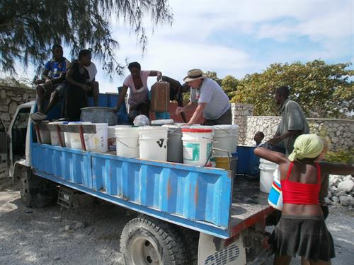 A truck loaded with 5 gal pails from a village which does not have a pump. We have delivered thousands of gallons of water over the years such as this scene. 200 pails means 1000 gallons of water. We could use our entire time of just delivering water to dry areas. Usually on a Saturday one of our employees will use his own time and head for a village or a neighborhood. One Sat night the truck pulled into the compound at 8 o'clock from their last load of water. A total of 9 loads of water that day.