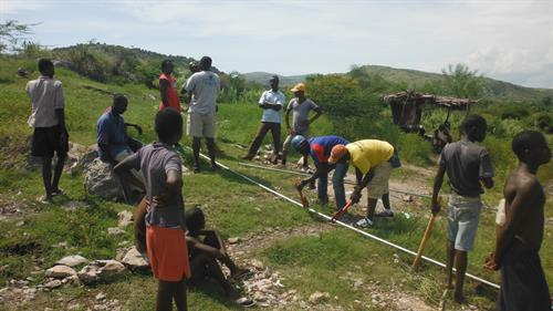 Laying pipe to a village cistern from an electric well.