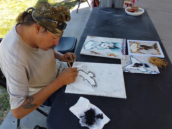 Dennis creates his Lakota artwork for observers in Whiteclay, NE.