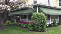 Striped Sunbrella porch awnings installed around a Lititz porch