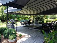 Stationary fabric canopy with rounded front edge installed over a patio