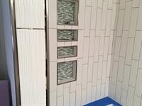 Bathtub installation with vertical subway tile and Schluter trim.
