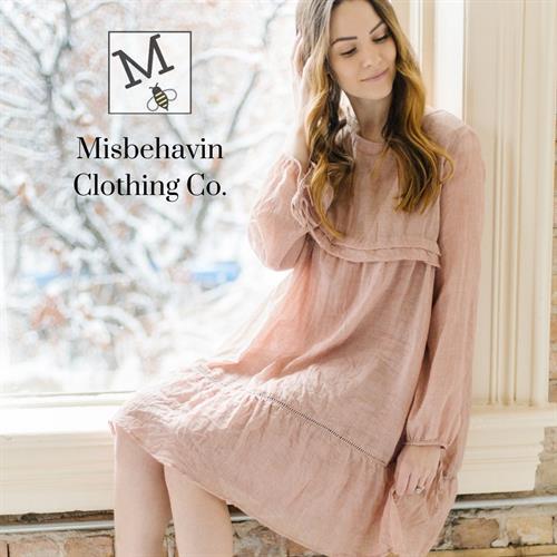 Misbehavin-Clothing-Co-Logo-Woman-Sitting-In-Window-Wearing-Pink-Boho-Dress