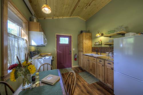 Each cabin features a compact but full kitchen with locally crafted custom cabinets, electric range, refrigerator/freezer, microwave, double sink, coffee makers, dishware, cookware, glassware, utensils, and even a small selection of pantry supplies: locally roasted coffee, organic teas, sweeteners, creamers, and spices.