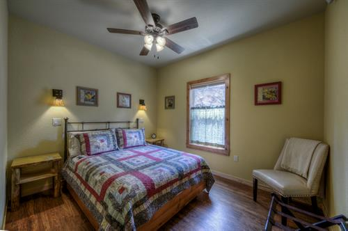 Bedroom feature comfy beds, cotton quilts, ceiling fans, Tiffany lighting, and room darkening shades.