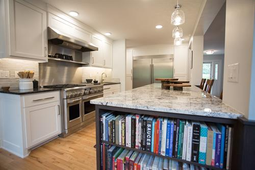 Beautiful and functional contrasting island storing a large collection of recipe books to be at the home owner chef's fingertips.