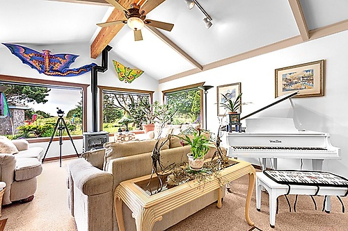 The Boreas living room has beautiful westward ocean views, cozy fireplace, baby grand, light and bright.