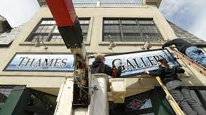 Installing the sign for the new Thames River Gallery on Bank Street after removing the original Gallery at Firehouse Square sign. Owner John Johnson closed the Gallery at Firehouse Square two years ago but has reopened it under the new name.