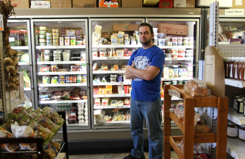 Caleb, Owner, poses in front of the dairy selection