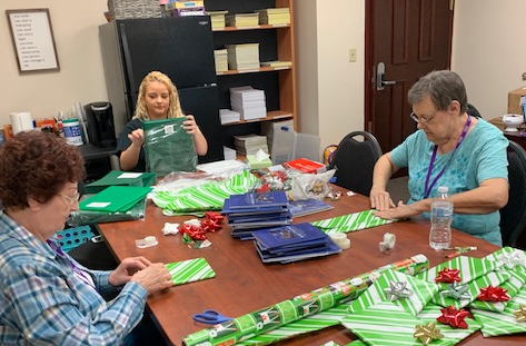 Volunteers are busy at VITAS wrapping holiday presents.