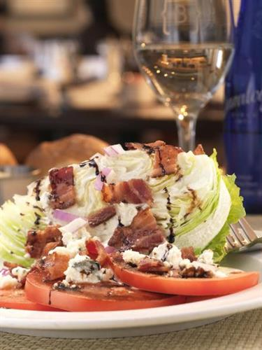 The Classic Wedge - chopped iceberg lettuce tossed with grape tomatoes, red onions and buttermilk blue cheese dressing, topped with applewood smoked bacon, blue cheese crumbles and balsamic reduction
