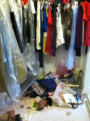 Unorganized women's walk-in closet Before Room Solutions By Paula