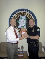 Barry donations Good Neighbears to Southaven Police Chief, Tom Long.