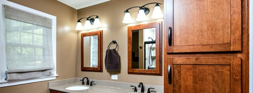 Solid cherry cabinets and matching mirrors in this Peoria, IL bathroom