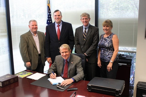 Dunwoody Mayor Denis Shortal (seated) signs the closing paperwork on the new Dunwoody City Hall building