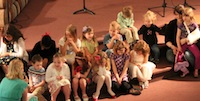 The children hear a story on Sunday morning from youth Brynna Sumey