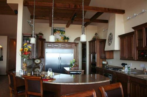 Vaulted ceiling with wooden beams, upgraded appliances, and granite counters