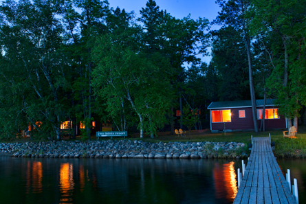 Lakeside view of the cabins at night.