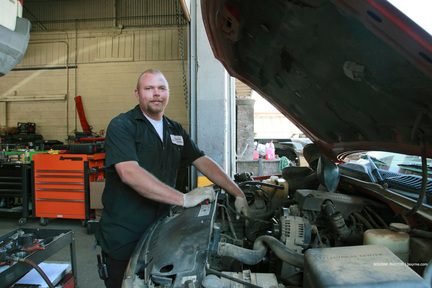 man posing for picture with hands working on car engine. auto shop in background.
