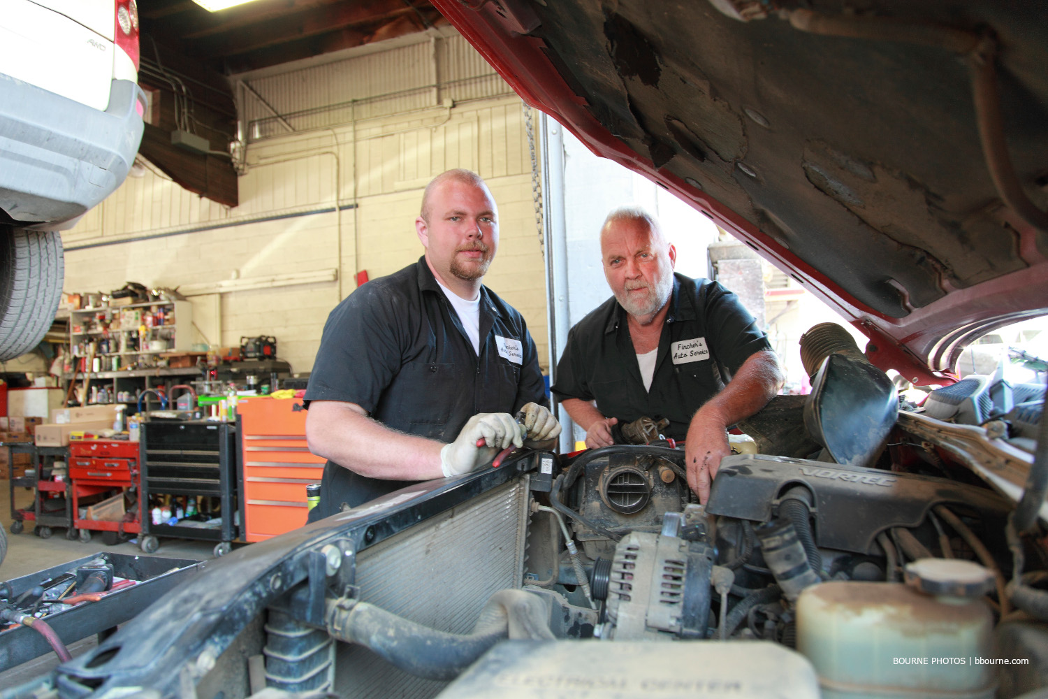 two men posing for picture while working on engine of a car in auto shop.