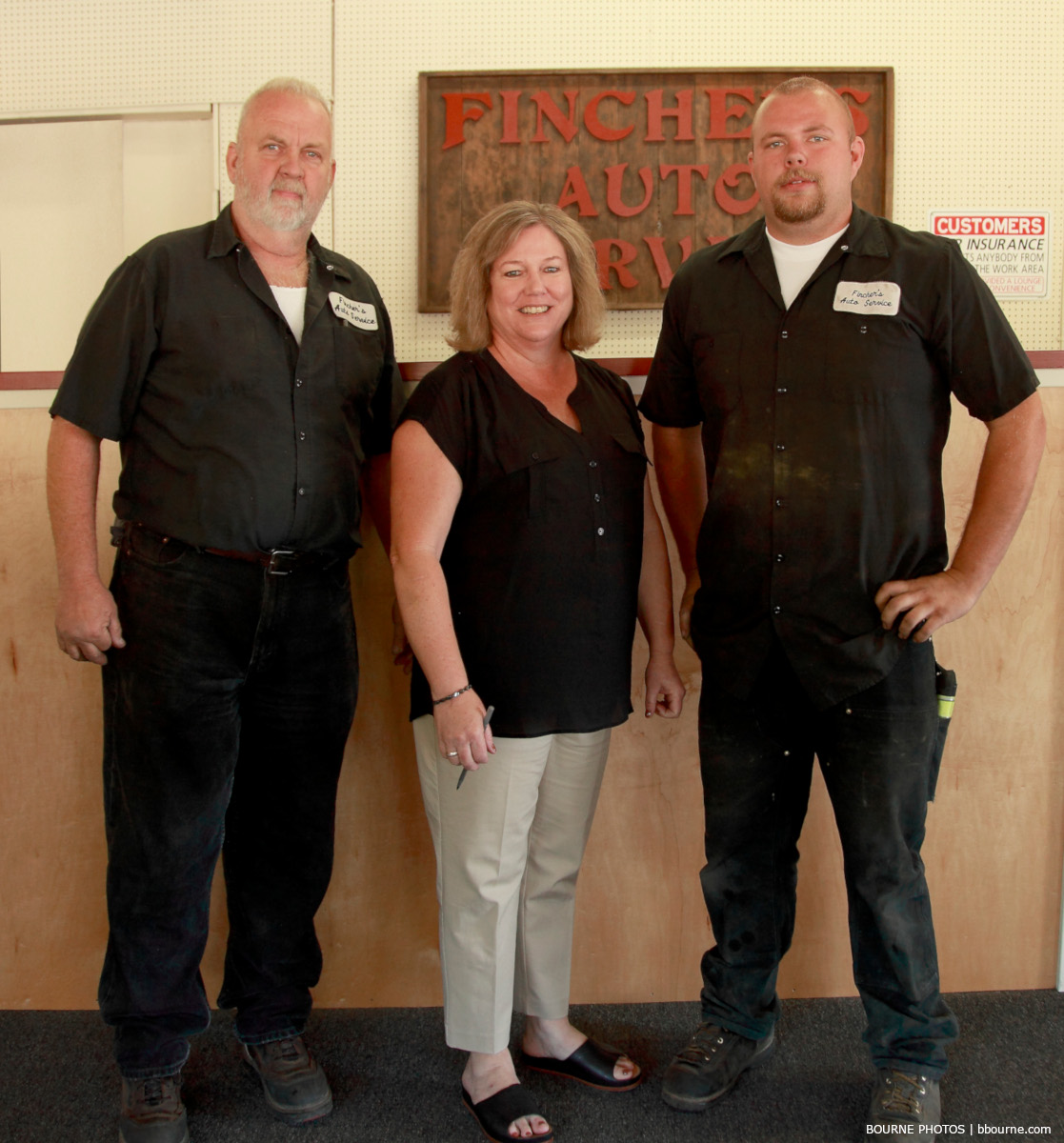 two men and one woman standing and posing for picture. finchers auto rv.