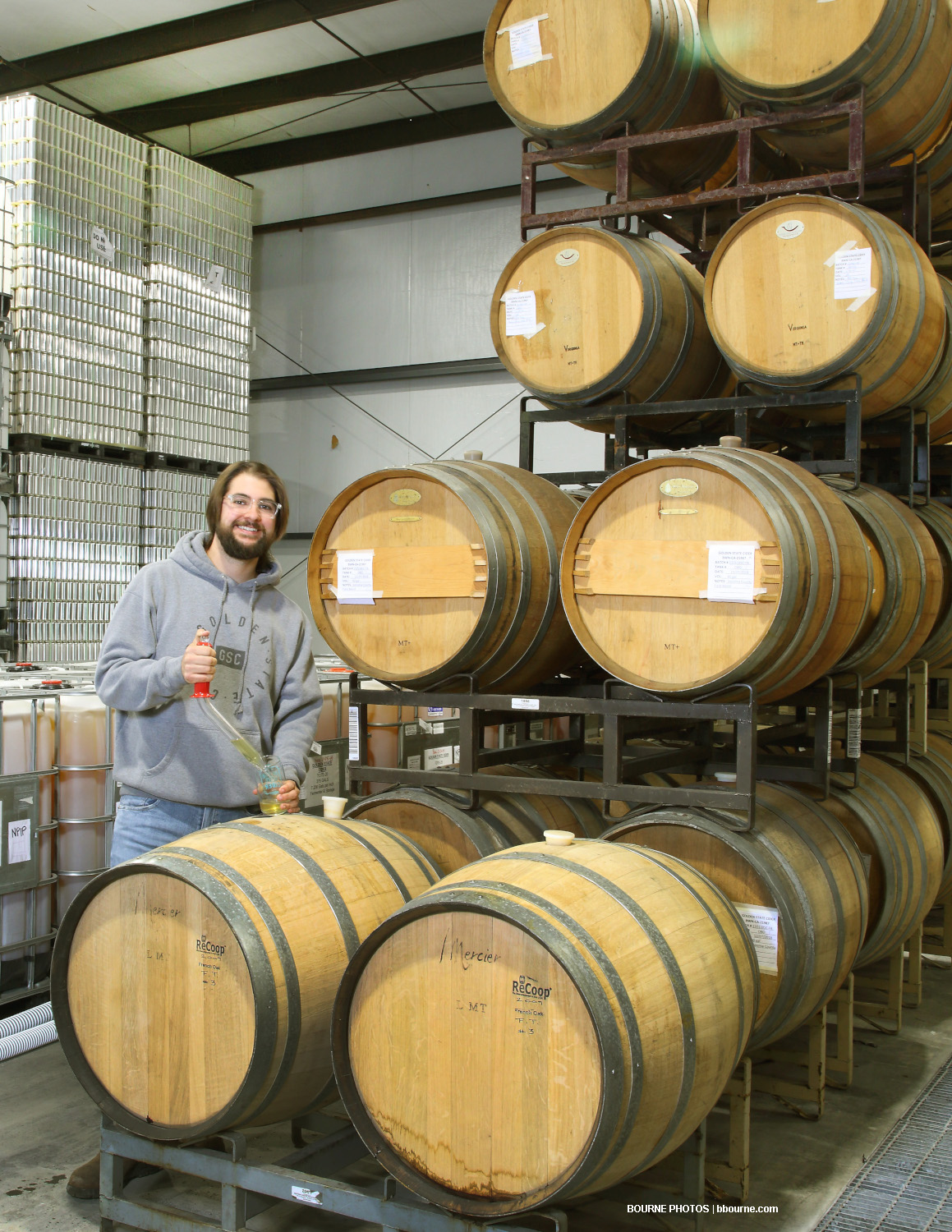 man standing in warehouse next to wooden barrels with cider, testing cider, with stacked cans in the background.
